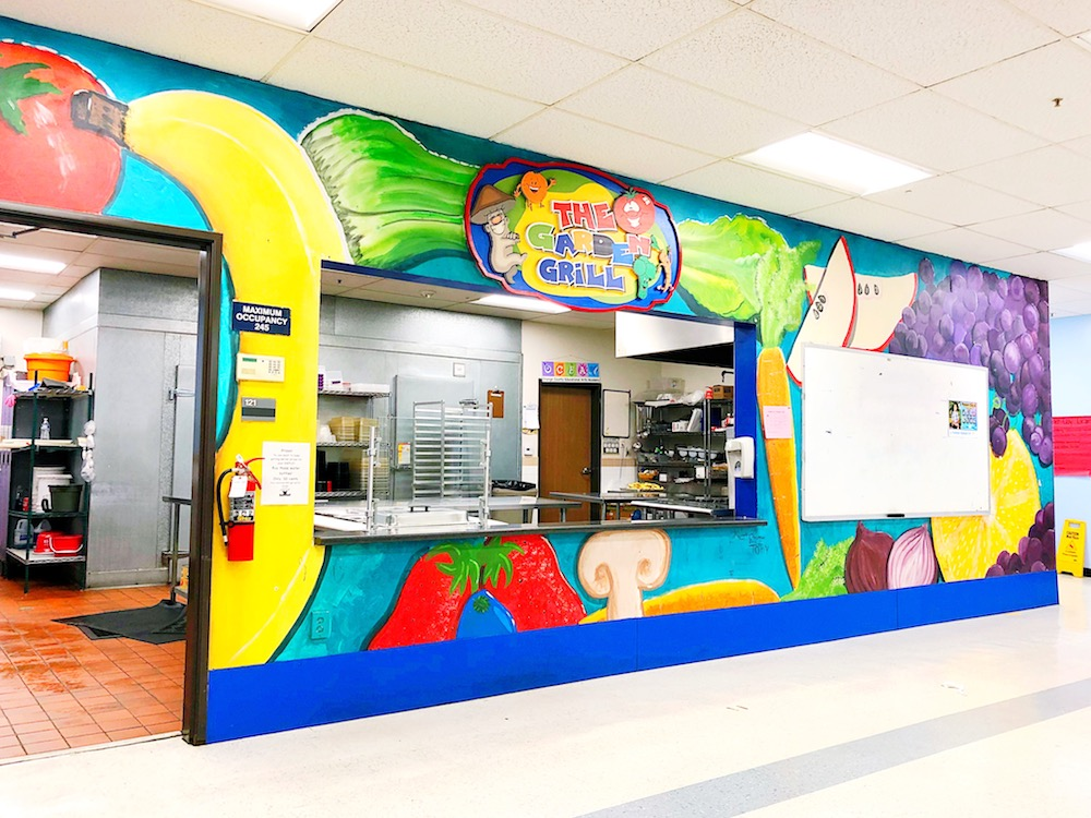Cafeteria mural featuring fruits and vegetables at a dual immersion school